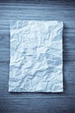 Wrinkled paper  on wood Royalty Free Stock Photo