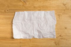 Wrinkled paper on wooden background royalty free stock photography