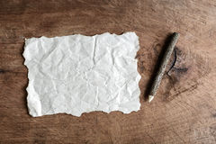 Wrinkled paper and wooden pencil on old wooden Royalty Free Stock Image