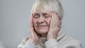 Wrinkled senior female suffering strong headache, massaging temples, healthcare. Stock footage stock footage