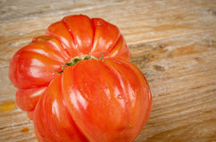 Wrinkled tomato. Of the particularly tasty Raf type on a rustic wooden table Stock Images