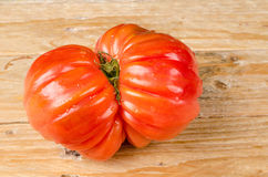 Wrinkled tomato. Of the particularly tasty Raf type on a rustic wooden table Royalty Free Stock Photo