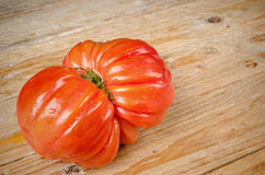Wrinkled tomato. Of the particularly tasty Raf type on a rustic wooden table Royalty Free Stock Image