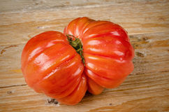 Wrinkled tomato. Of the particularly tasty Raf type on a rustic wooden table Royalty Free Stock Photos