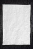 Wrinkled White paper on dark wood Stock Image