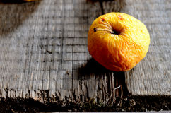 Wrinkled yellow apple on a board Royalty Free Stock Photo