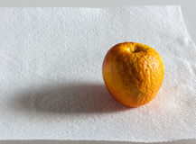 Wrinkled yellow apple on white paper towel Stock Images