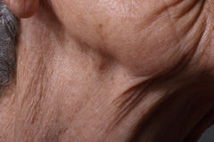Wrinkles. On the chin and neck of an elderly woman royalty free stock images