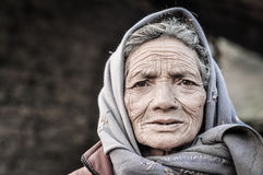 Wrinkles in Nepal. Dolpo, Nepal - circa May 2012: Old woman with wrinkles on her face and brown eyes wears grey headcloth in Dolpo, Nepal. Documentary editorial Stock Photos