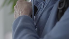 Wrinkly arms fixing backpack at the back. Mature woman in blue hoody. Wrinkly arms fixing black backpack at the back stock footage