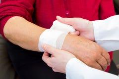 Wrist bandaging. Photo of doctor bandaging the elderly woman wrist royalty free stock photos