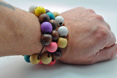 Wrist with 3 beaded bracelets jewellery. Wrist with three beaded wooden bracelets on jewellery with a light blue background Royalty Free Stock Photography