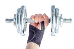 Wrist damage rehabilitation. Hand in brace holding metal dumbbell royalty free stock photos