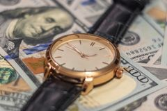 Wrist gold watch lie on the bills of 100 dollar money. Soft focus stock photo