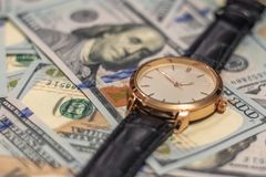 Wrist gold watch lie on the bills of 100 dollar money. Soft focus. royalty free stock photos