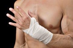 Wrist injury. Closeup of shirtless male athlete with injured wrist bandaged in sports wrap on black background stock photos