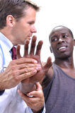 Wrist injury. White medical doctor tests pain tolerance of young athletic black man's wrist on white background royalty free stock photo