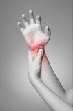 Wrist pain. A young woman massaging her painful wrist stock photo