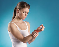 Wrist pain. Young woman holding her painful wrist over blue background. Sprain pain location indicated by red spot royalty free stock image