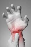 Wrist pain. A young woman massaging her painful wrist stock image