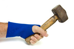 Wrist Support. Male hand wearing blue neoprene wrist support using heavy hammer over white Stock Photography