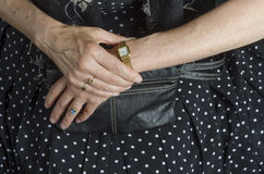 Wrist Watch. Close-up of an older woman's hands consulting a classic gold wristwatch. Her hands rest on a simple black leather purse Stock Photography