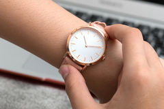Wrist watch on girl`s hand in front of a notebook computer Stock Photography