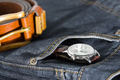Wrist watch and leather belt on jeans Royalty Free Stock Photos