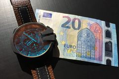 Wrist watch with leather strap near the banknote on a dark background, watch on top of money, time is money, wristwatch, European. Currency, twenty euros royalty free stock photo