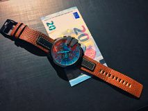 Watch with leather strap near the banknote on a dark background, watch on top of money, time is money, wristwatch, European. Wrist watch with leather strap near stock photography