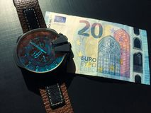 Watch with leather strap near the banknote on a dark background, watch on top of money, time is money, wristwatch, European curren. Wrist watch with leather royalty free stock images