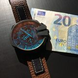 Watch with leather strap near the banknote on a dark background, watch on top of money, time is money, wristwatch, European curren. Wrist watch with leather stock photography