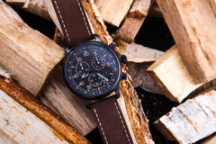 Wrist watch men& x27;s brown leather strap on wood. Wrist watch men& x27;s brown leather strap on wood. Black dial Stock Images