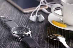 Wrist watch and mobile phone with headphones and a cup of coffee on a dark wooden table stock images