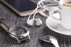 Wrist watch and mobile phone with headphones and a cup of coffee on a dark wooden table stock photos