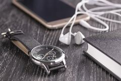 Wrist watch, mobile phone with headphones and notepad on an old dark office desktop. Old dark office desktop with elements for business and work. Wrist watch royalty free stock photo