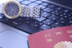 Wrist watch and a passport  over keyboard Stock Image
