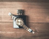 Wrist watch with perfume on a wood background. Royalty Free Stock Photo