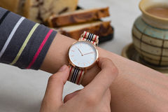 Wrist watches on girl`s hand at the coffee break. Girl`s hand with wrist watches at the coffee break in front of hot chocolate and cake Stock Photos