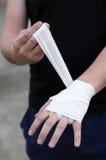 Wrist wraps. Male boxer putting on white wrist wraps Royalty Free Stock Image