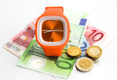 Wristlet watch with banknotes and coins. Wristlet watch with banknotes 10, 20 and 100 euro on a white backgound Royalty Free Stock Image
