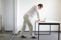 Wrists exercise durring office work. Standing man reading at tablet in his office Stock Image