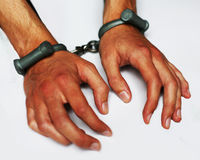 Wrists and hands in handcuffs. Mans hands locked in regulation barrel handcuffs Royalty Free Stock Photography