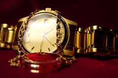 Wristwatch. Gold wrist watch with a gold chain on burgundy background Stock Photography