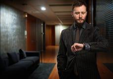 Όμορφο άτομο που εξετάζει το wristwatch Στοκ εικόνα με δικαίωμα ελεύθερης χρήσης