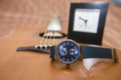 Wristwatch i gitara akustyczna w tle Zdjęcia Royalty Free