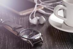 Wristwatch i telefon komórkowy z hełmofonami i filiżanka kawy na ciemnym drewnianym stole fotografia royalty free