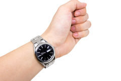 Wristwatch on left wrist. Silver wristwatch with black front surface on left wrist on white background Stock Photo