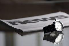 Wristwatch and newspaper Stock Photo