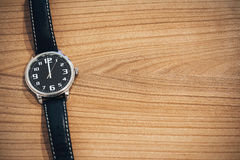 Wristwatch at noon time. Wristwatch on wooden table with blank space for text on the right side - clock face show the time at noon or midnight Stock Image